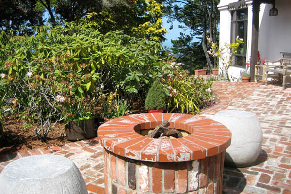 Brick patio and gas fire pit surrounded by Rhododendron gardens.