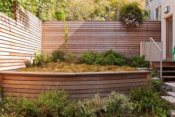 Low-maintenance native plants and a redwood retaining wall maximize ease-of-use in this 375 sq. ft. city back yard.