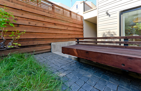 Basalt split-cube cobbles and custom redwood bench.